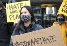 """Trish Villanueva (C) of Seattle holds a sign with the hashtag """"stop AAPI hate"""" during the We Are Not Silent rally organized by the Asian American Pacific Islander (AAPI) Coalition Against Hate and Bias in Bellevue, Washington on March 18, 2021. (Photo by Jason Redmond / AFP) (Photo by JASON REDMOND/AFP via Getty Images)"""