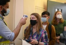 A health worker takes the temperature of a student in a queue to receive a dose of the Pfizer/BioNTech Covid-19 vaccine at a vaccination centre in London on June 5