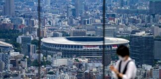 A person takes a picture from an observation deck as National Stadium, where the opening ceremony of the Tokyo Olympics will be held, is seen in the background in Tokyo.