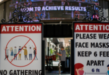 FILE: Signs with social distancing guidelines and face mask requirements are posted at an outdoor mall amid the COVID-19 pandemic in Los Angeles.