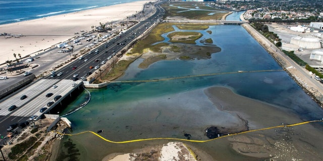 An aerial photo shows floating barriers known as booms to try to stop further incursion into the Wetlands Talbert Marsh after an oil spill in Huntington Beach, Calif., on Huntington Beach, Calif., on Monday, Oct. 4, 2021. A major oil spill off the coast of Southern California fouled popular beaches and killed wildlife while crews scrambled Sunday, to contain the crude before it spread further into protected wetlands. (AP Photo/Ringo H.W. Chiu)