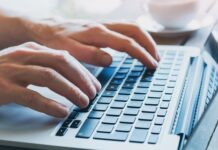 Close up of hands of business person working on computer, man using internet and social media (iStock).